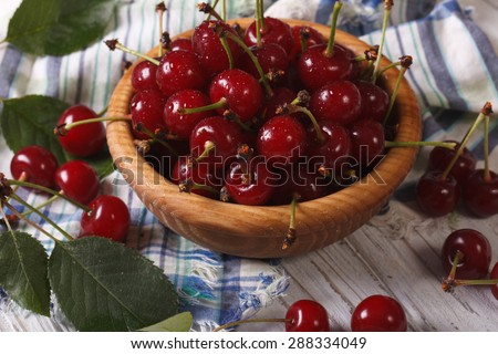 Ripe juicy cherries in a wooden bowl closeup. horizontal, rustic