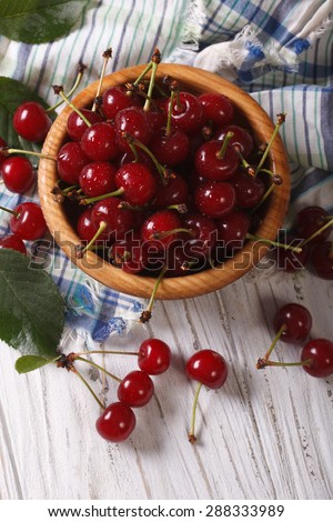 Ripe juicy cherries in a wooden bowl closeup. vertical view above, rustic style