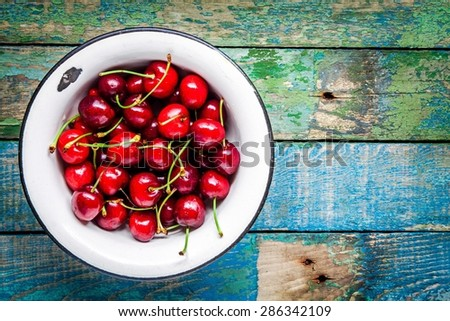 ripe juicy cherry in  an old bowl  on a rustic wooden table - stock photo