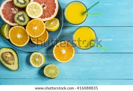 ripe juicy citrus fruit juice ice on a blue wooden table top view - stock photo