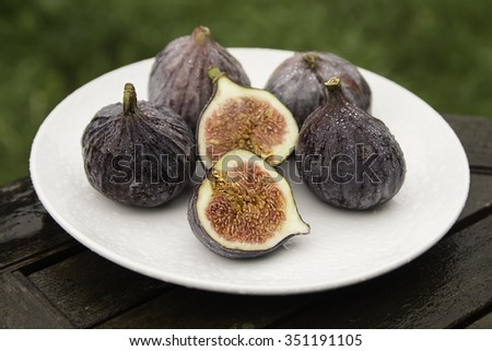 Ripe juicy figs lying on a plate. Four whole figs, one cut in half. - stock photo