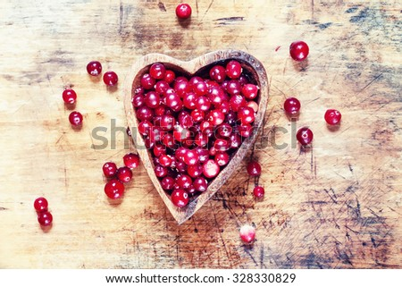 Ripe juicy fresh cranberries in Moscow in the form of heart on the old wooden background, top view