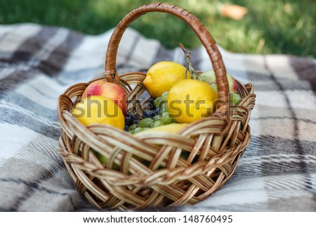 Ripe juicy fruits in basket on wooden table - stock photo