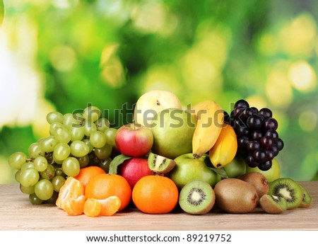 Ripe juicy fruits on wooden table on green background - stock photo