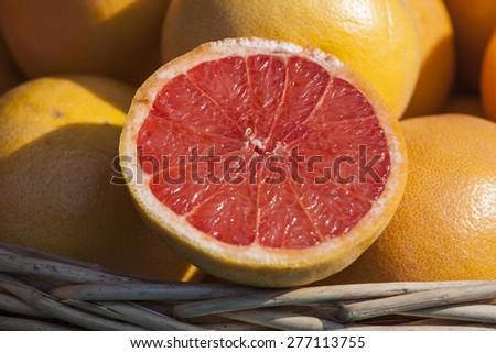 Ripe juicy grapefruits on a show-window of shop of vegetables and fruit and a grapefruit half - stock photo
