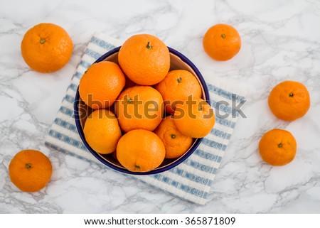 Ripe juicy mandarin fruit in enamel bowl with napkin on white marble - stock photo