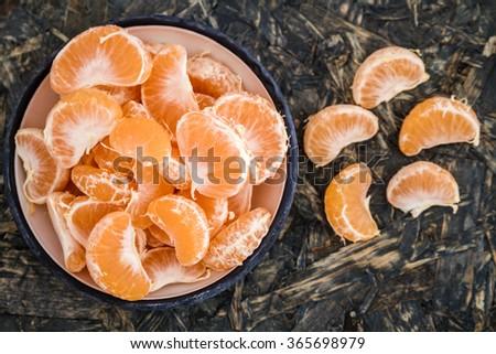 Ripe juicy mandarin fruits in enamel plate on blue wooden background - stock photo