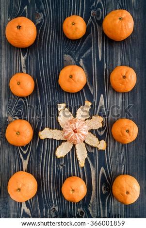 Ripe juicy mandarin fruits on blue wooden background - stock photo