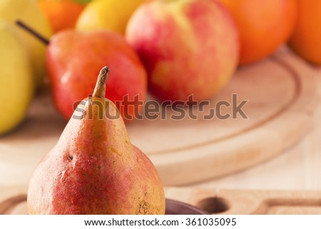Ripe juicy pear on a wooden board - stock photo