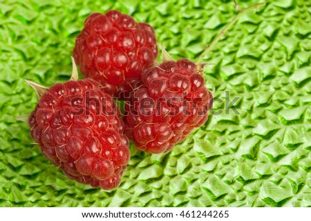ripe juicy raspberries on green abstract background