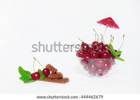 Ripe juicy red cherry with mint and chocolate in a glass bowl with decoration on white background closeup. Still life. The natural background. - stock photo