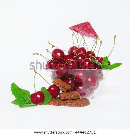 Ripe juicy red cherry with mint and chocolate in a glass bowl with decoration on white background closeup. The natural background. - stock photo