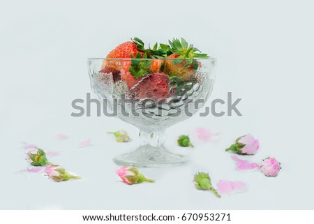 Ripe juicy strawberries in a glass bowl. Little rosebuds around.