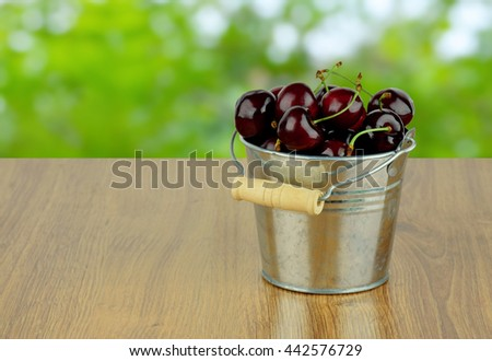Ripe juicy sweet cherries in a small metal bucket on a wooden background with a blurred natural background. Season goodies. Snack. Diet. Natural vitamins. - stock photo