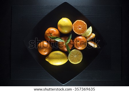 Ripe juicy tangerine, orange mandarin and lemon with leaves on black plate. - stock photo