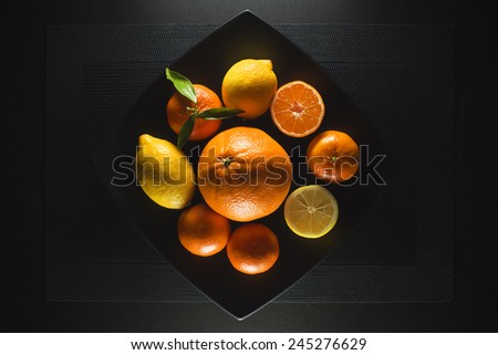 Ripe juicy tangerine, orange mandarin and lemon with leaves on black table - stock photo
