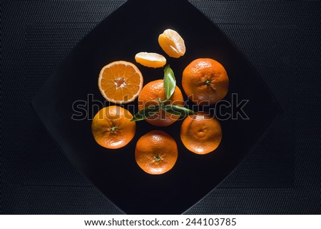 ripe juicy tangerine, orange mandarin with leaves on black table - stock photo