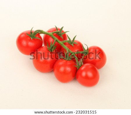 Ripe juicy tomatoes/Juicy Vine Tomatoes/A photo of juicy and ripe vine tomatoes shot on a textured beige color canvas tablecloth. Shot in Studio. - stock photo