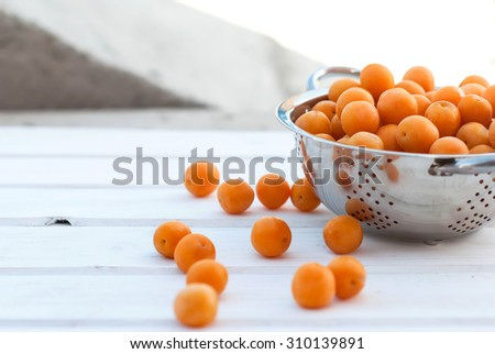 ripe juicy yellow plums in a colander on a white board selective focus - stock photo