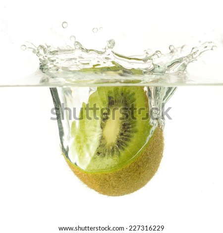 Ripe kiwi falling into water, splashes all around. - stock photo