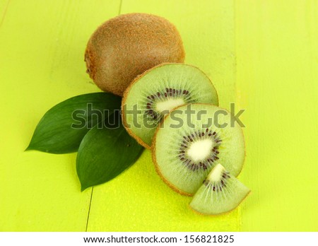 Ripe kiwi on green wooden table close-up