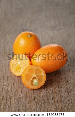 ripe kumquat fruits on wooden table, exotic fruit
