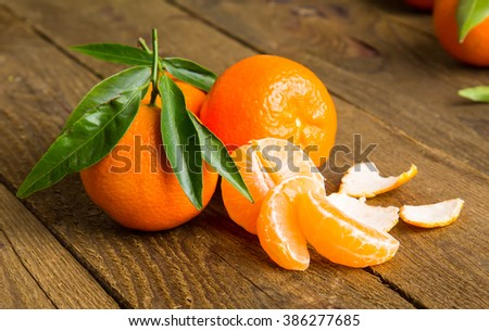 Ripe Mandarin fruit peeled open and place on old rustic look timber with group of mandarin fruits and leaves out of focus on the background - stock photo