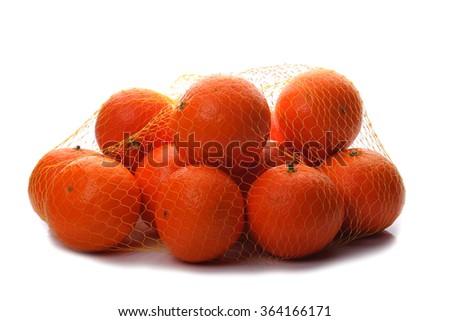 Ripe mandarins in string bag isolated  on white - stock photo