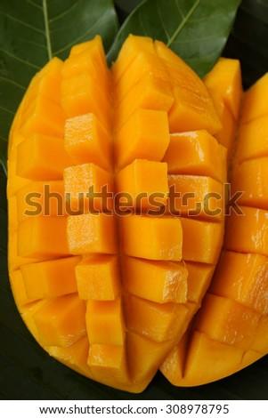 Ripe mango, cube cut on banana leaf. - stock photo