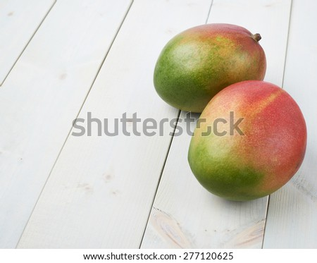 Ripe mango fruit lying over the white colored wooden board surface as a background composition
