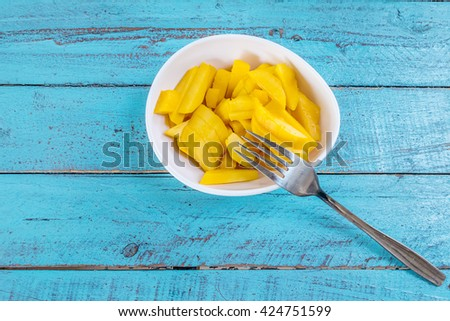 Ripe mango slices in a cup  on a blue wooden table with a fork. - stock photo