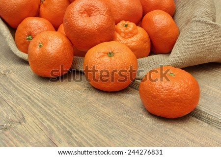 Ripe Moroccan Tangerines  in Burlap Bag on Grunge Wood Table - stock photo