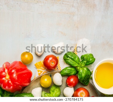ripe multicolor tomatoes, mozzarella balls with basil leaves and oil in white bowl on rustic wooden background, top view, place for text - stock photo