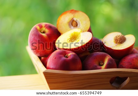 ripe nectarines and peaches on wooden basket