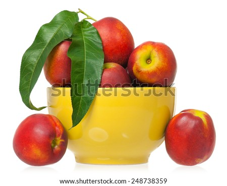 Ripe nectarines in the yellow bowl isolated on a white background - stock photo