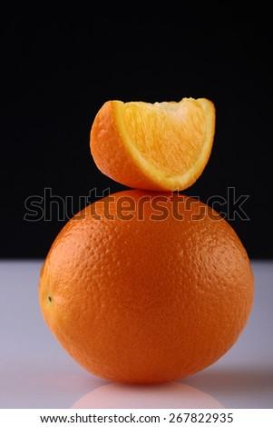 Ripe orange fruit and orange slice with reflection on black background - stock photo