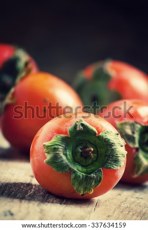 Ripe orange persimmons on an old wooden table in rustic style, selective focus - stock photo