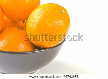 Ripe oranges in a black bowl - stock photo