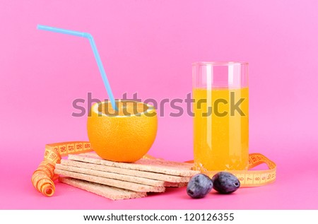 Ripe oranges, loafs and  juice as symbol of diet on pink background - stock photo