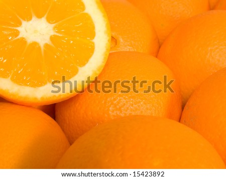 ripe oranges pile with an orange sliced