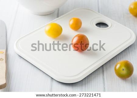 ripe organic colorful mini tomats on white chopping board - stock photo