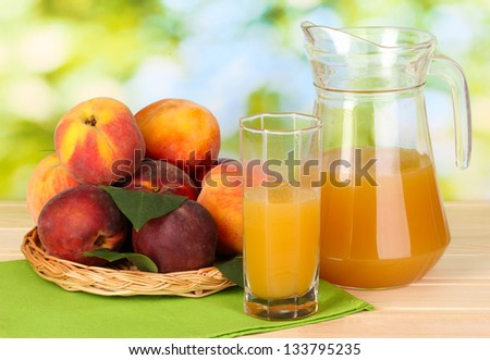 Ripe peaches and juice on wooden table on natural background