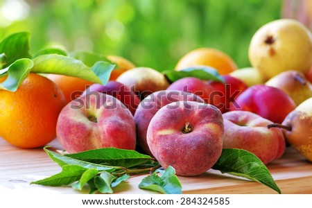 Ripe peaches and pears, oranges, on table - stock photo