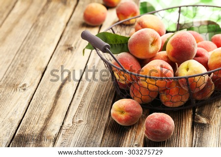 Ripe peaches fruit in basket on a brown wooden background - stock photo