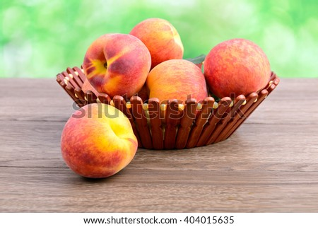 Ripe peaches in basket on green background - stock photo