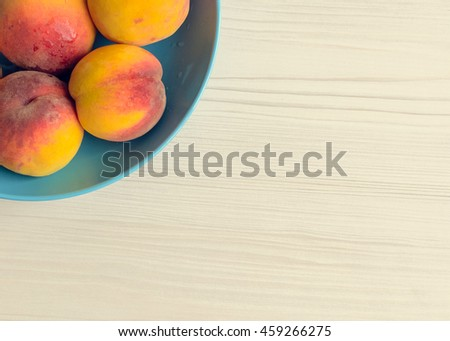 Ripe peaches in blue bowl on white wooden background. Group of fresh peaches on white table. Juicy and fresh peach with place for text. Concept for healthy eating and nutrition. Top view. Copy Space. - stock photo