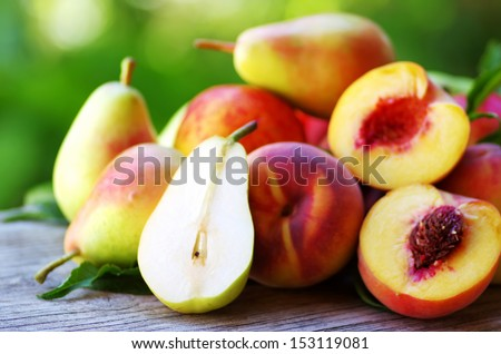 Ripe pears and peaches on table - stock photo