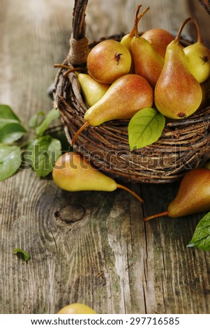 Ripe pears in a basket on a wooden background.  Selective focus - stock photo