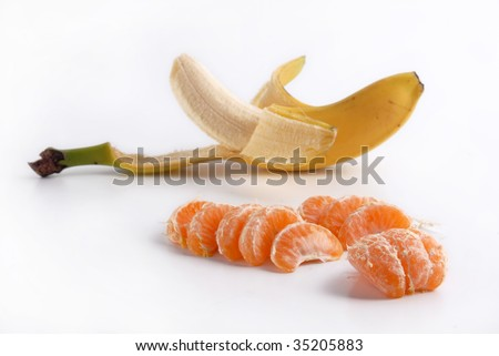 Ripe peeled banana and juicy tangerine slices on the floor