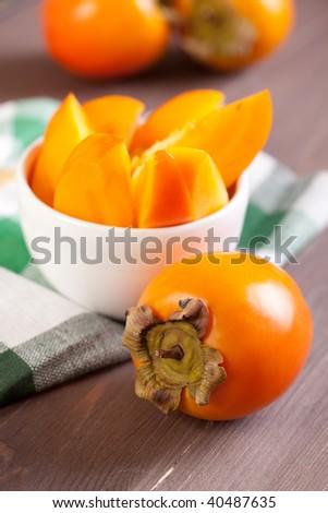 ripe persimmon on wooden table. shallow dof - stock photo